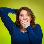 Closeup portrait, headshot startled woman, looking shocked, surprised, covering mouth with hand, unexpected situation isolated green background. Human emotion, facial expression feeling reaction disbelief